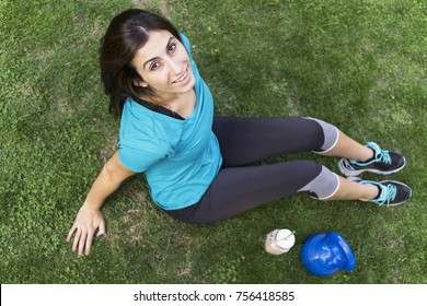 Happy young woman relaxed pose after exercise. Fitness concept, sport shoes, kettlebell on grass.