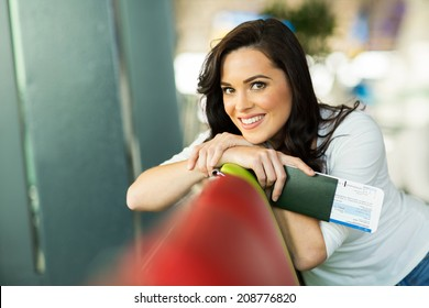 happy young woman relaxing at airport before boarding