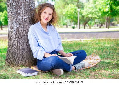 Happy young woman relaxing with book in summer park. Jolly beautiful girl with curly hair sitting with crossed legs on blanket and smiling at camera. Preparing for university entry concept