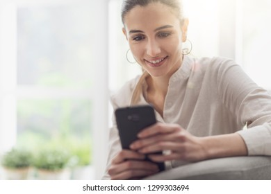 Happy young woman relaxing at home she is sitting on the armchair and chatting with her touch screen smartphone
