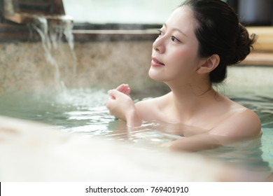 happy young woman relaxing in hot springs and using hand to bailing water