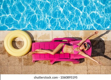 Happy young woman relaxing on sun bed by the pool