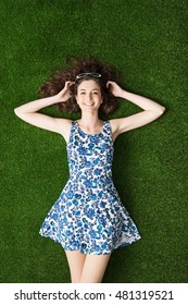 Happy young woman relaxing on the grass and lying down with hands behind head, relaxation and nature concept