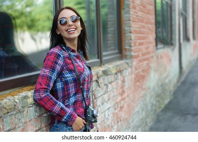 Happy young woman resting near building