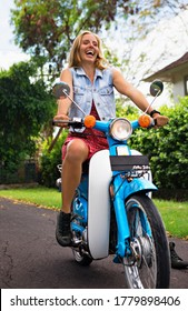 Happy young woman ride on rental custom retro motorbike in road journey around tropical island. Travel adventure lifestyle, recreational activities at summer cruise holidays. Asian trip background