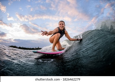 happy young woman rides the wave on surf style wakeboard and touches the wave with one hand