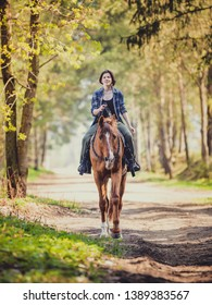 happy young woman riding horse with cordeo in the morning in spring forest