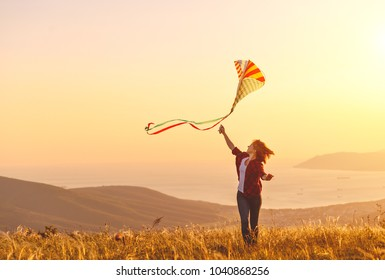 Happy young woman running with a kite on a glade at sunset in summer
