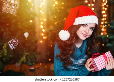 Happy young woman in santa hat near christmas tree. Merry Christmas and Holidays!