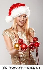 Happy young woman in Santa's hat holds red christmas balls.
