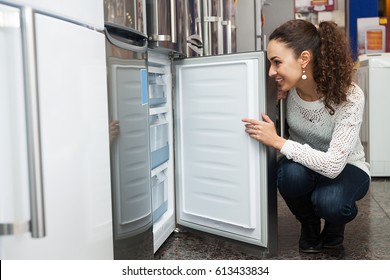Happy young woman selecting domestic refrigerator in supermarket