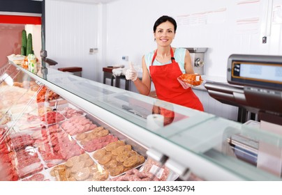 happy young woman seller showing different sausages in butcher's shop