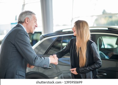 Happy young woman shaking hands to the salesman and choosing her new car in a showroom