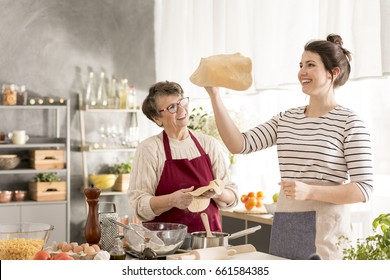 Happy, young woman shaping pizza dough while cooking with grandma