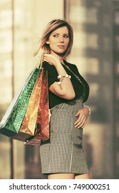 Happy young woman with shopping bags at the mall Stylish fashion model outdoor