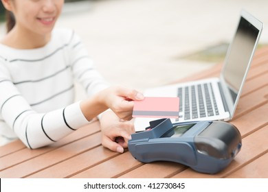 Happy young woman shopping and paying on internet by credit card with laptop computer pc, asian beauty