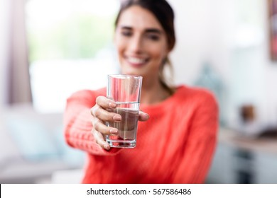 Happy young woman showing drinking glass with water at home