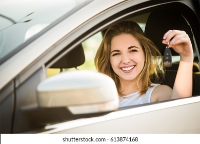 Happy young woman showing keys from her first car - side view