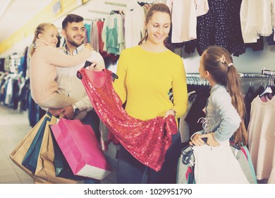 Happy young woman showing new red dress to daughter during family shopping