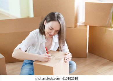 Happy young woman signs carton box with goods and chattels, moving to the new home concept