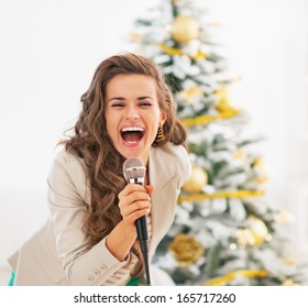 Happy young woman singing with microphone in front of christmas tree