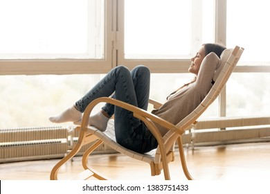 Happy young woman sit relaxing in comfortable rocking chair feel peaceful enjoy sun near big windows, smiling girl lying with eyes closed rest in rocker spend calm sunny morning at home living room