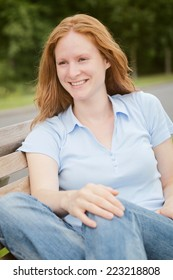 A happy young woman sits on a bench in a park in summer and looks sideways with a smile on her face.