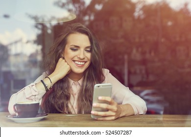 Happy young woman sitting in coffee shop texting on her smart phone