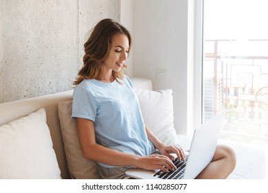 Happy young woman sitting on a couch at home with laptop computer