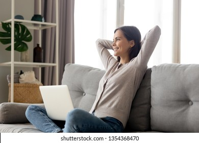 Happy young woman sitting on couch put hands behind head spends lazy weekend resting at home comfortable sofa, use laptop, communicating dating online, freelance finish work, relaxing dreaming concept