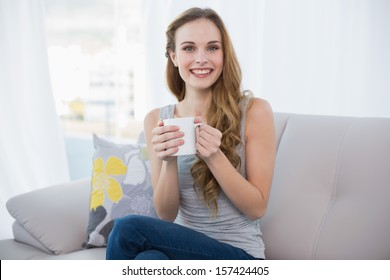 Happy young woman sitting on sofa holding a mug at home in the living room