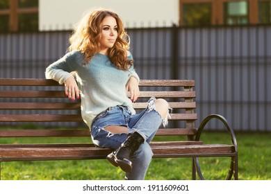 Fröhliche junge Frau auf der Bank Stilvolles Modemodell in zerrissenen Jeans und hellblauer Pullover