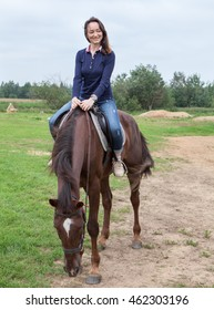 Happy young woman sitting on chestnut horse while riding on field