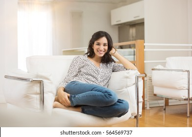 Happy young woman sitting on sofa at home and looking at camera. Portrait of comfortable young woman in casual relaxing on armchair. Portrait of beautiful woman smiling while sitting on couch at home.