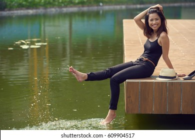 Happy young woman sitting on wooden pier and splashing water with her legs