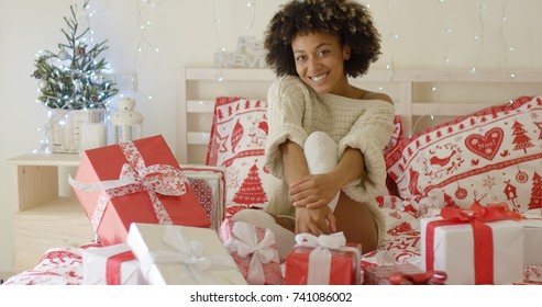 Happy young woman sitting on her bed surrounded by Christmas gifts holding one out to the camera with a lovely smile