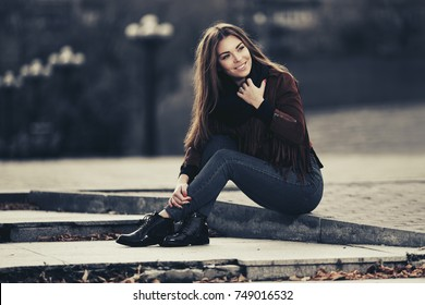 Happy young woman sitting on the sidewalk in city street Stylish fashion model in a fringe leather suede jacket and blue jeans
