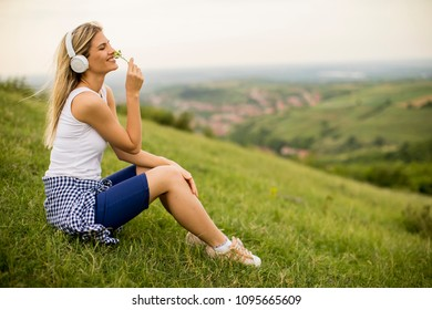 Happy young woman sitting outside on grass and listening to music on headphones