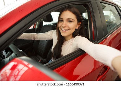Happy young woman sitting in red car and making selfie. Beautiful girl with chestnut hair smiling and looking at camera. Pretty female customer making purchase of automobile.