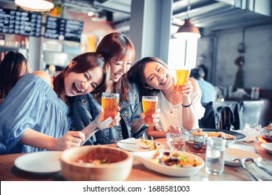 happy young woman sitting in  restaurant and enjoy dinner and beer