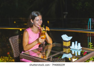 Happy young woman sitting in the rooftop bar with cocktail in night time.
