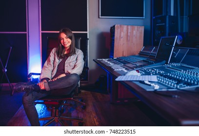 Happy young woman sitting in sound recording studio. Female music composer sitting by sound mixing console.