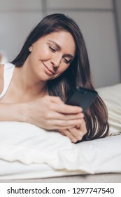 Happy young woman with smartphone texting message in bed at home in the morning