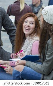 A happy young woman smiles as she sits with her firends studying outdoors. She is holding a digital tablet and laughing with friends.