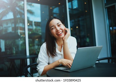 Happy young woman smiling in cafe,Portrait Smiling Asian woman using laptop in coffee shop.
