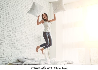 Happy young woman is  smiling jumping on bed with pillows in hands