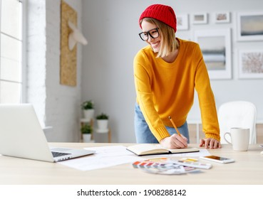 Happy young woman smiling for laptop and writing in planner while leaning on table during work on project at home