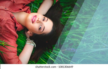 Happy young woman smiling layed in grass above shot with copy space for text close-up portrait