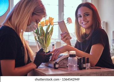 Happy young woman smiling an looking at a camera in a beauty salon, holding a phone while manicure master doing beauty procedure