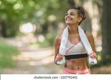 Happy young woman smiling at park after exercise. Portrait of young woman with towel around neck looking at camera. Beautiful young woman feeling energetic after yoga and exercise outdoor